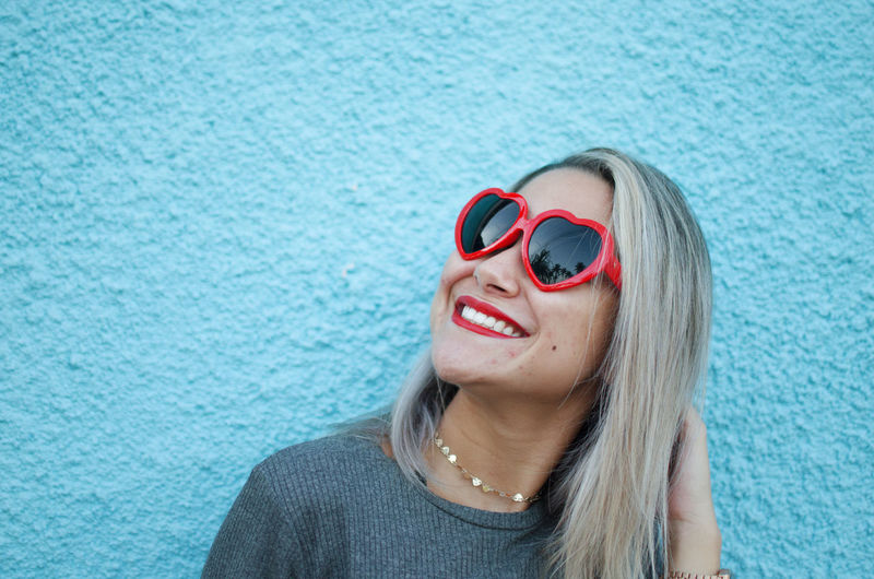 One Person Fashion Glasses Sunglasses Headshot Portrait Lifestyles Women Leisure Activity Smiling Real People Hair Blue Young Women Day Front View Young Adult Happiness Emotion Hairstyle Beautiful Woman Outdoors Red Heart