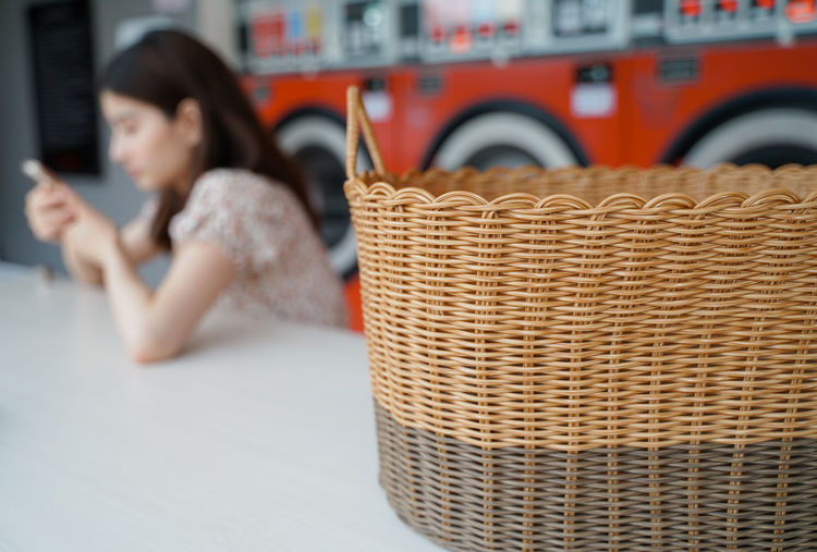 Midsection of woman sitting in basket