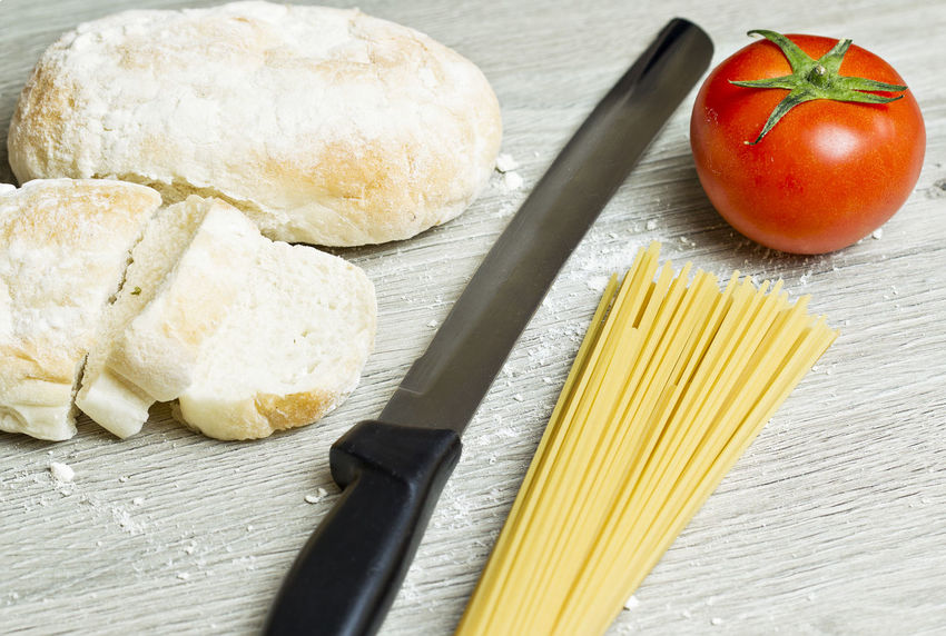 sliced bread with loose flour and tomatoes,spaghetti on a wooden board Bread Cereal Plant Close-up Cultures Food Food And Drink Freshness Healthy Eating Indoors  Ingredient Italian Food No People Spaghetti Wheat Wholegrain Wood - Material