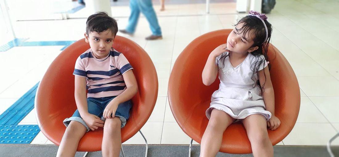 Portrait of cute siblings sitting on seats