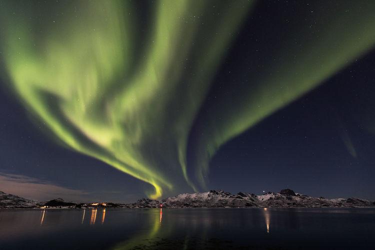 Scenic view of aurora borealis over lake at night