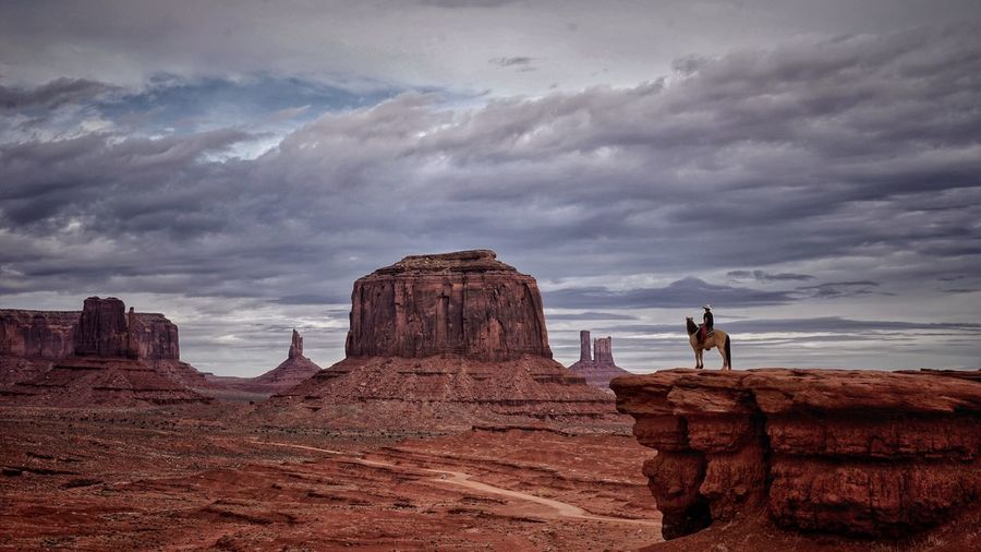 Man With Horse On Mountain Against Cloudy Sky