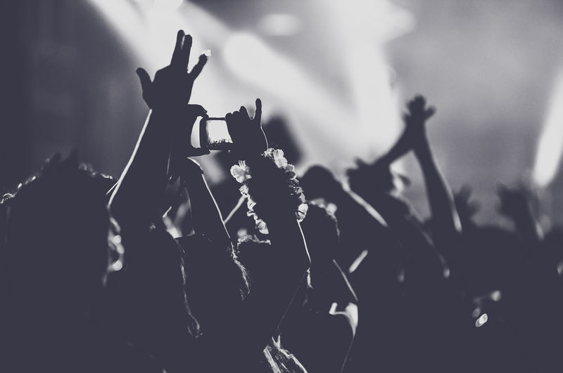Silhouette People With Arms Outstretched Standing At Music Concert