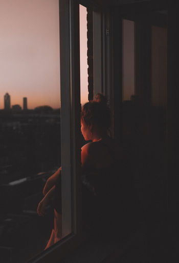 Side view of thoughtful depressed woman looking through window at sunset