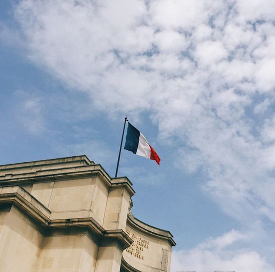 Low angle view of flag waving on building against sky