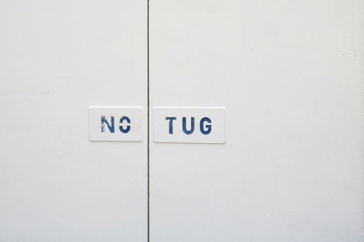 No Tug sign on side of ship Blue Words No Tug Graphics Ship Cruise Ship White Background White Travel Photography Sign Ocean Tug Boat