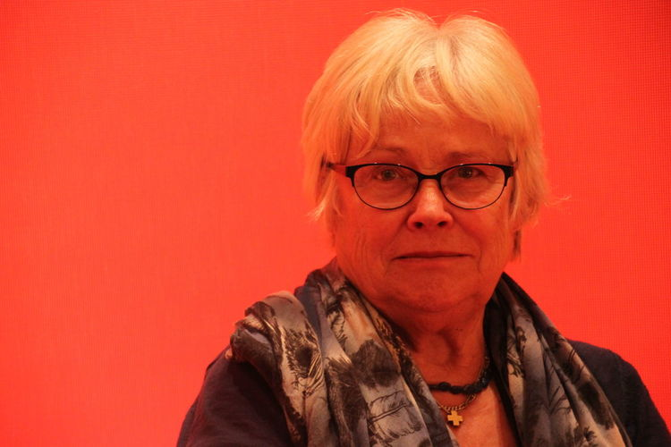 Portrait Of Senior Woman Against Orange Background
