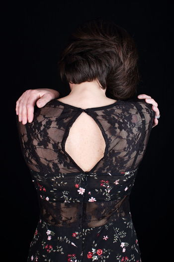 Rear view of woman wearing dress against black background