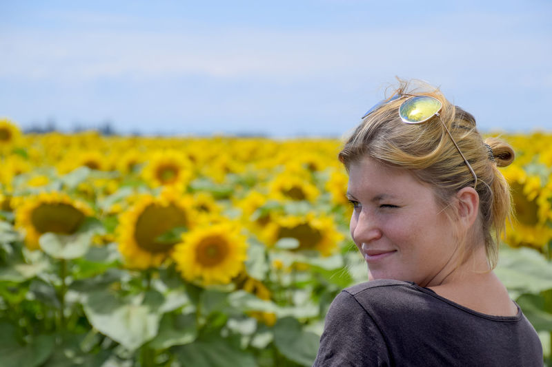 Woman Winking While Standing Against Sunflowers Field
