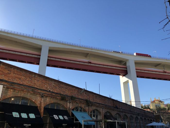 Low angle view of road bridge against clear blue sky in Lisbon, Portugal Lisbon Portugal Built Structure Architecture Building Exterior Sky Low Angle View Clear Sky Building Blue Nature Day No People City Bridge Bridge - Man Made Structure Residential District Outdoors Copy Space Connection House Window