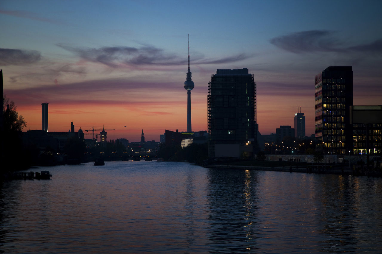 River by fernsehturm against sky during sunset