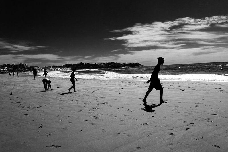 Man walking on beach against sky