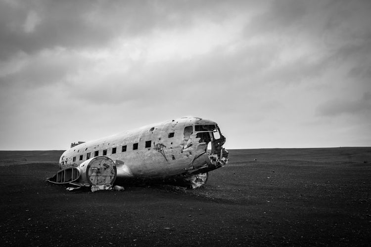 Abandoned airplane on airport runway against sky