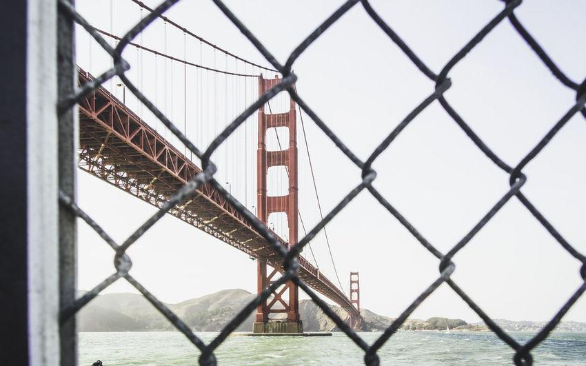 Bridge over chainlink fence against sky