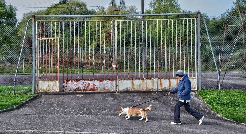 Full length of man with dog walking on road by abandoned gate