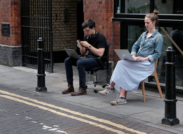 People sitting on chair with mobile phone