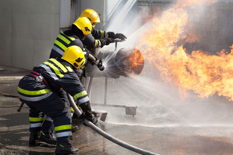 Firefighters attack a propane fire during a training exercise Adult Adults Only Courage Danger Day Emergency Equipment Firefighter Headwear Heat - Temperature Helmet Men Only Men Outdoors People Protective Mask - Workwear Protective Workwear Rescue Worker Smoke - Physical Structure Work Helmet Working