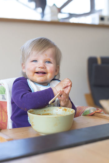 Portrait of blonde toddler eating in highchair Childhood Child Portrait Meal Toddler  Baby Girl Porridge Smiling Blonde Caucasian Eating At Home Innocence Having Fun Tooth Table Kitchen Education Feeding  Face Sitting Spoon Mess Messy Kid Dinner Dish Cute Lifestyles Laughing Bib German European  Boy Unfiltered Authentic Moment One Person Highchair High Chair