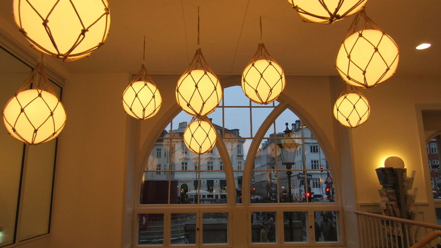 Low angle view of illuminated pendant lights hanging in building