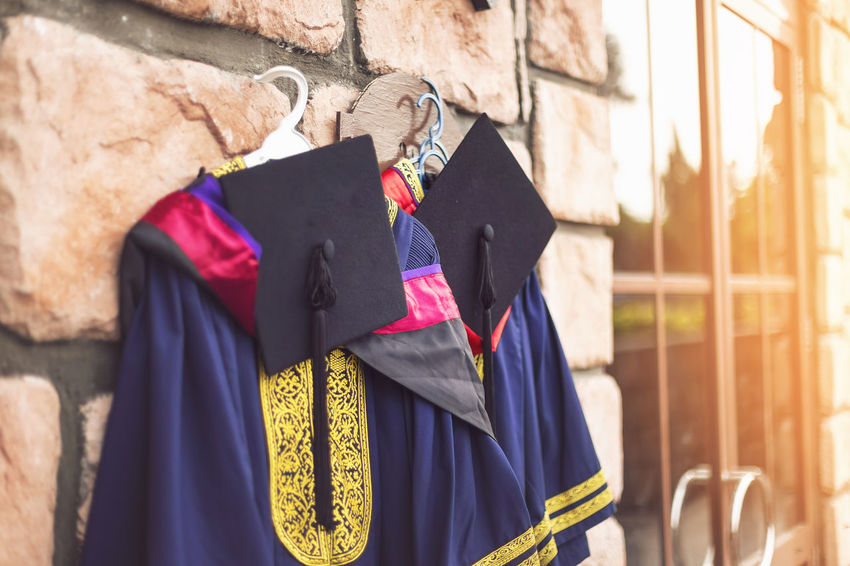 Graduation day concept. casual clothing hanging at the wall Academic Bachelor Casual Clothing Certificate College Concept Convo Convocation Day Degree Diploma Dress Education Exam Graduate Graduation Happy High School Idea Ideas Professional School Student Success Sunny University