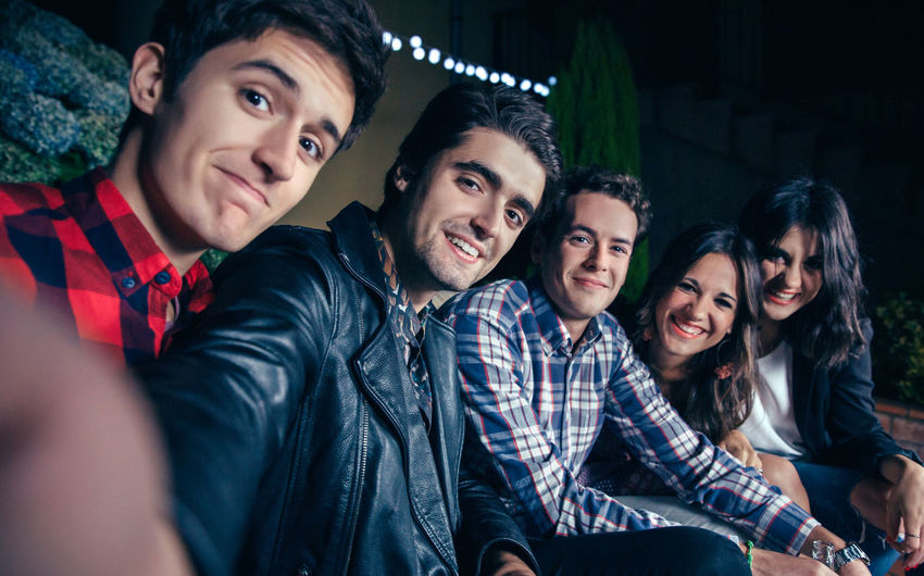 Group of happy young friends smiling while taking a selfie photo in a outdoors party. Friendship and celebrations concept. Celebration Friends Fun Happiness Happy Horizontal Looking At Camera Millenials Young Alcohol Cheerful Drink Entertainment Five People Friendship Grimace Group Night Nightlife Outdoors Party People Selfie Smiling Sofa