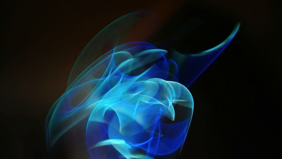 Close-up of blue light painting against black background