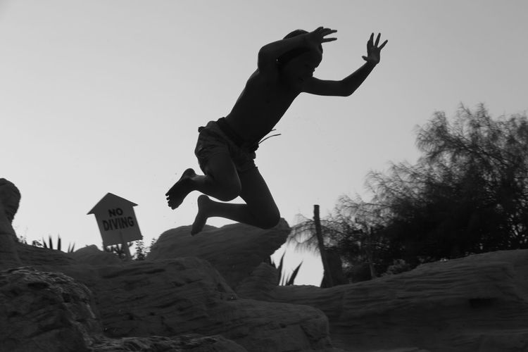 Low angle view of boy in mid-air by rock formations against sky