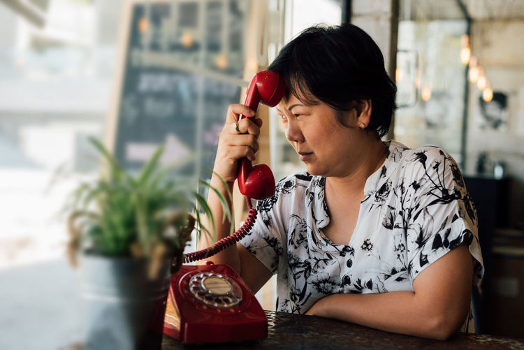 Serious woman holding telephone receiver by table