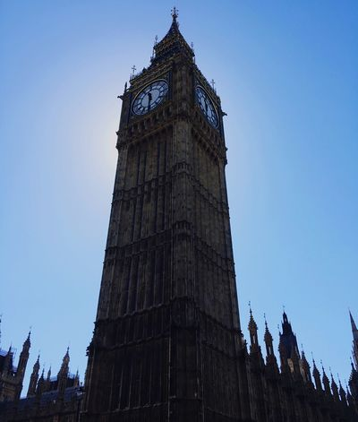 Elizabeth Tower, also known as Big Ben, towering above the Palace of Westminster, amongst radiating sunlight. Big Ben Westminster Elizabethtower United Kingdom Tourists History Sun Sunlight