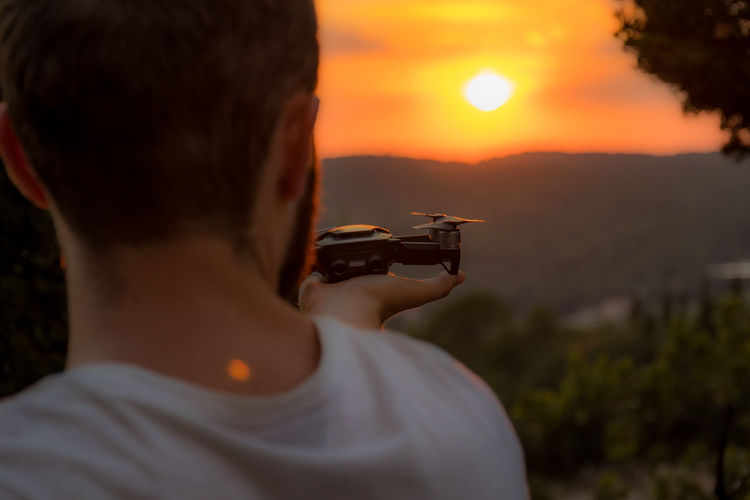 Rear view of man holding camera against sky during sunset