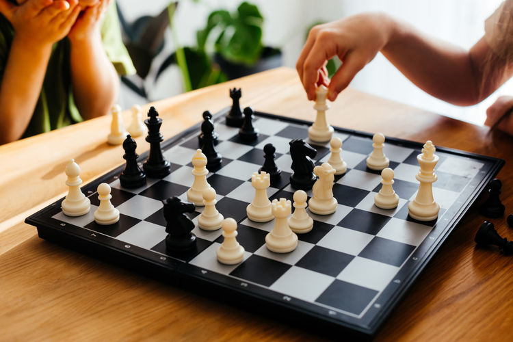 Low section of person playing on chess board