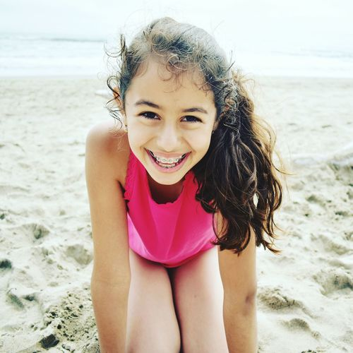 Close-up portrait of cheerful girl kneeling at beach