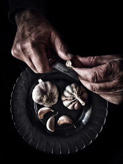 Directly above of man peeling garlic against black background