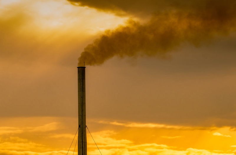 Low angle view of smoke emitting from chimney against sky during sunset