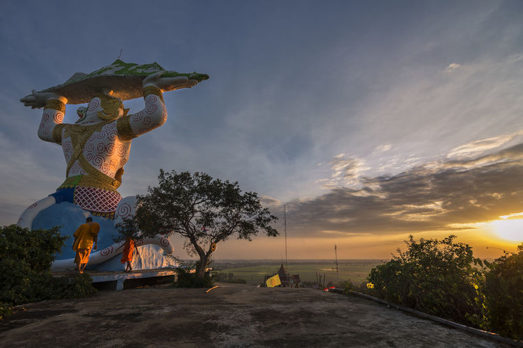 Statue by tree against sky during sunset