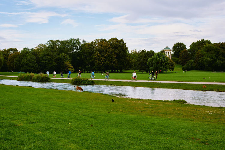 People in park by lake against sky