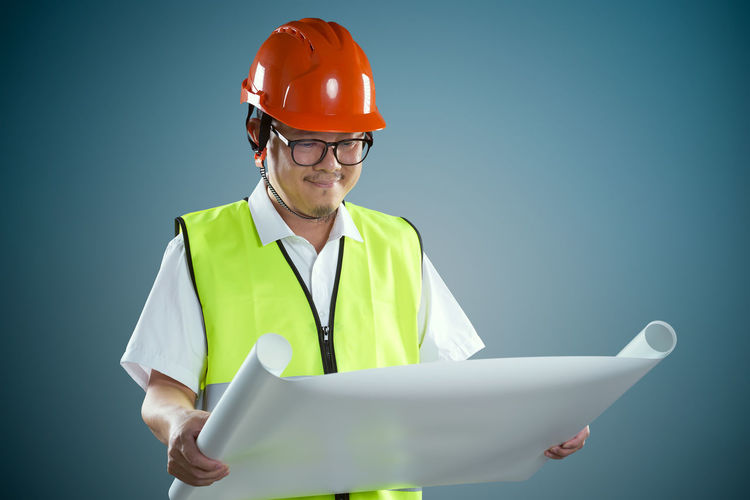 Worker Looking At Chart While Standing Against Colored Background