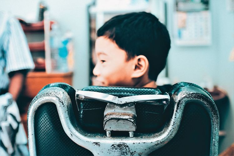 Rear view of smiling boy sitting on chair at barber shop