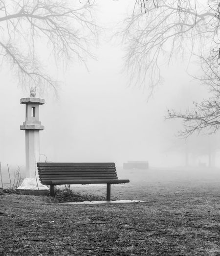 Empty Bench By Stone Lantern On Field At Park During Foggy Weather
