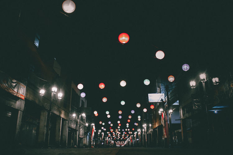 Illuminated lanterns hanging in city at night