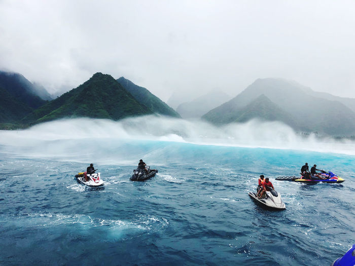 People on boat in sea against mountains