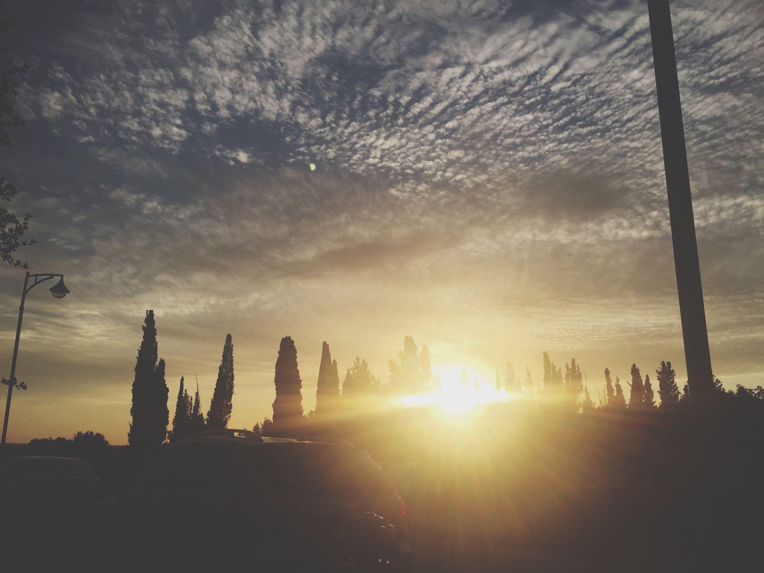 sun, silhouette, sunset, sky, sunbeam, architecture, built structure, cloud - sky, sunlight, lens flare, building exterior, low angle view, back lit, cloud, travel destinations, outdoors, nature, cloudy, religion, tree