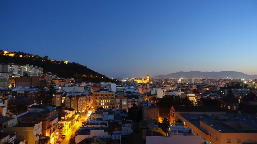 High angle shot of illuminated townscape against sky at dusk