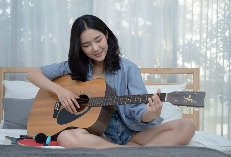 Smiling young woman playing guitar at home