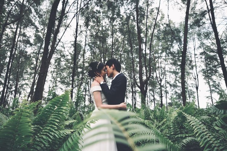 Young couple kissing in forest
