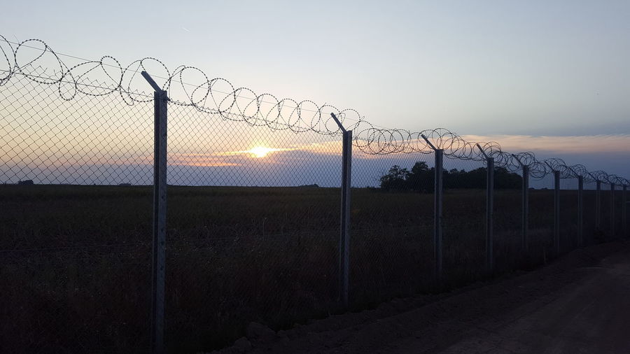 View Of Border Separated By Barbed Wire Against Clear Sky