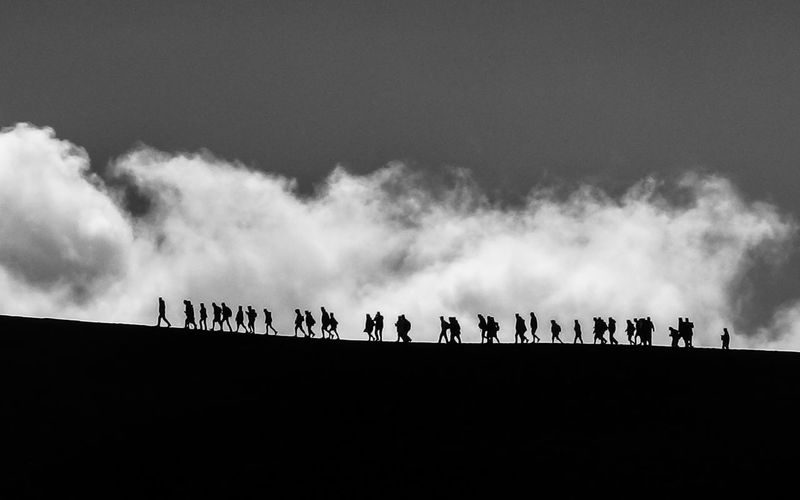 Silhouette people on land against sky