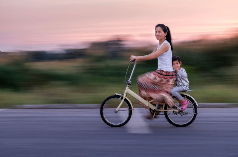 Blurred motion of woman and girl on bicycle