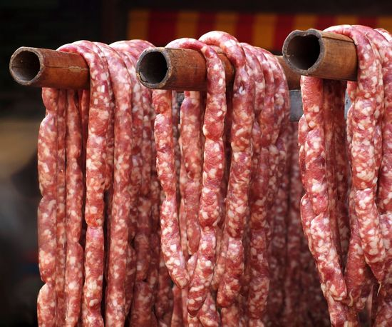 Handmade sausages at a local outdoor sausage grill stall hang on bamboo poles Casing Chain Fat Fresh Hand Made Handmade Meat Pork Sausage Chain Sausages Stall Street Food Worldwide Vendor
