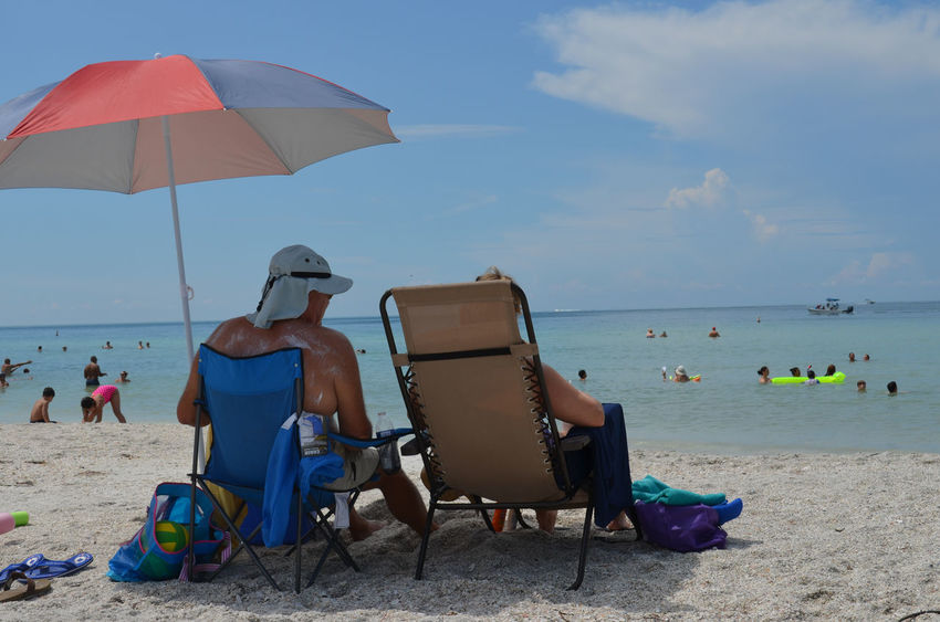 People at the beach American People Beach Chair Enjoyment Holidays Hot Day Lifestyles Real People Rear View Recreational Pursuit Relaxation Sand Sea Strand Summer Sunny Sunshine Tourism Tourist Tourists Vacation Vacations